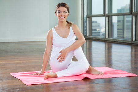 Full length of a happy young woman in Half Spinal Twist pose on mat Stock Photo - 15450015