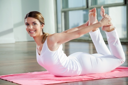 Portrait of a happy young woman practicing yoga exercise called Bow Pose Stock Photo - 15449990