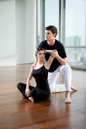 Yoga male instructor teaching yoga positions to young woman at gym Stock Photo - 15449977