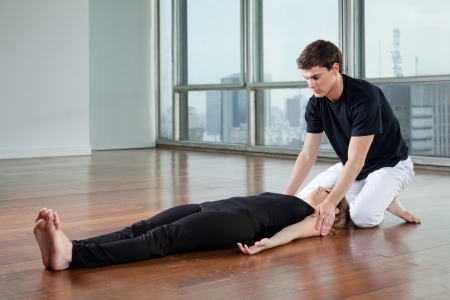 Young male yoga instructor helping female trainee at gym photo