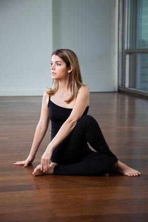 Full length of a young woman practicing yoga called Half Spinal Twist on wooden floor photo