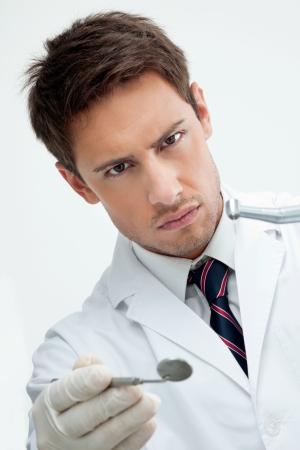 角度のついた: ドリルと斜めミラーを保持している若い男性の歯科医の肖像画
