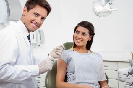 dentist s office: Portret szczęśliwa młoda dentysty męskiej trzyma nić natomiast pacjent patrzy na niego w klinice