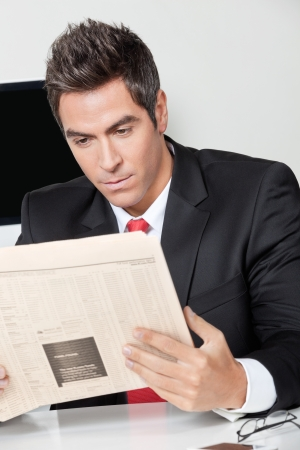 Young businessman reading newspaper at desk in office photo