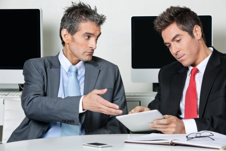 Young businessman using digital tablet while sitting with colleague at desk in office Stock Photo - 16056554
