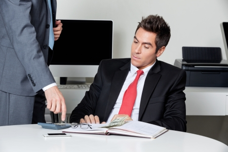 Businesspeople calculating finances at desk in office Stock Photo - 16056569