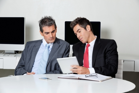 Two businessmen using digital tablet at desk in office Stock Photo - 16056518