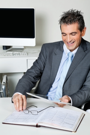 Happy mid adult businessman looking at digital tablet in office Stock Photo - 16056625