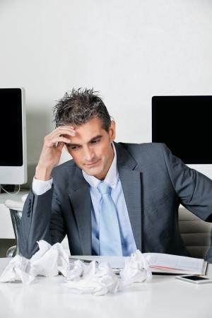 tensed: Tensed mid adult businessman sitting at desk in office