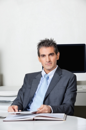 Portrait of businessman with digital tablet sitting at desk in office Stock Photo - 16056516