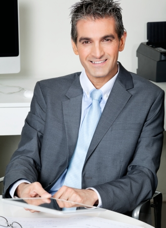 Portrait of businessman with digital tablet sitting at desk in office Stock Photo - 16056623