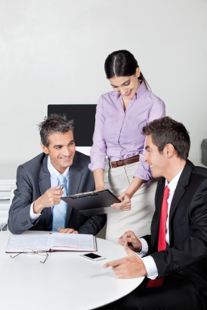 Three happy businesspeople in meeting at office Stock Photo - 16056524