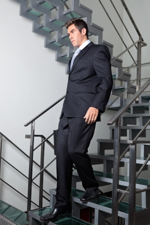 descending: Young businessman walking down the stairs at office Stock Photo