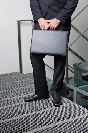 Low section of young businessman carrying briefcase by steps photo