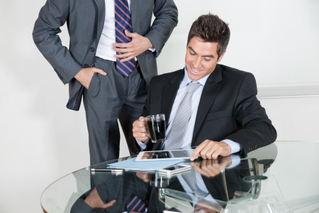 Businessman using digital tablet in a meeting with colleague at office Stock Photo - 16056521