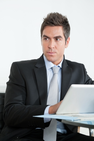 Handsome young businessman in suit using digital tablet at desk in office photo