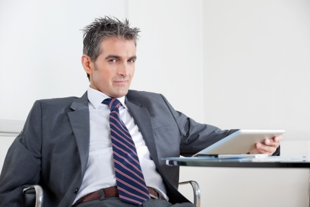 Portrait of mid adult businessman using digital tablet at desk in office Stock Photo - 16056513