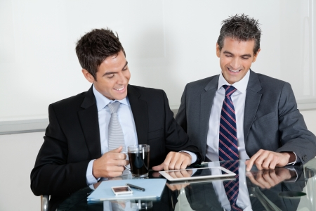 Two happy businessmen using digital tablet at desk in office photo