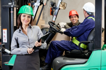 workplace safety: Portrait of smiling female supervisor with foremen communicating at warehouse