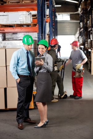 Female supervisor and male colleague using digital tablet with foremen communicating at warehouse photo