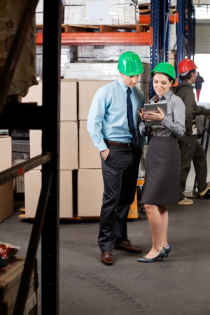 Young female supervisor and colleague using digital tablet at warehouse photo