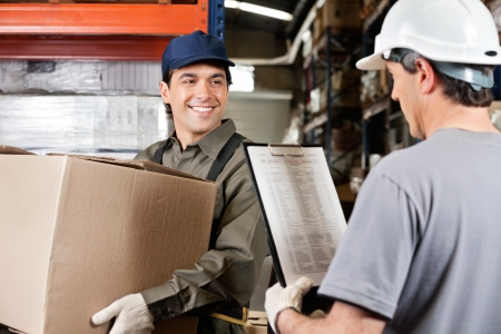 workplace safety: Young warehouse worker with cardboard box looking at male supervisor with clipboard