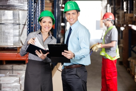 Portrait of supervisors with clipboard and foreman unloading cardboard boxes at warehouse Stock Photo - 16056497