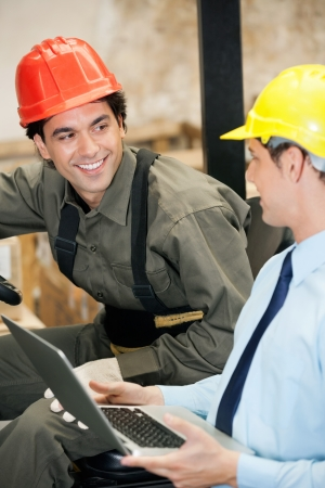Young male supervisor and forklift driver with laptop at warehouse photo