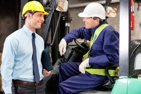 Young forklift driver communicating with supervisor at warehouse photo