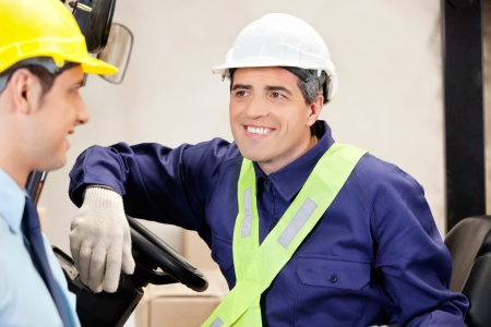 Happy forklift driver looking at male supervisor Stock Photo - 16056566