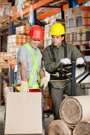 sack truck: Foreman with handtruck showing something to coworker at warehouse Stock Photo