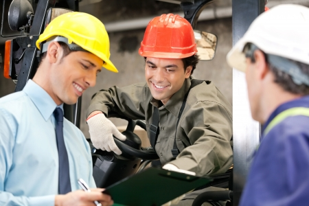 industrial safety: Happy young forklift driver with supervisor holding clipboard at warehouse