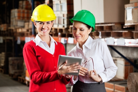 Portrait of female supervisor with colleague working together in warehouse photo