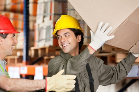 Happy foreman with coworker lifting cardboard box at warehouse photo