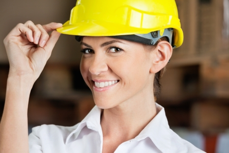 Portrait of an attractive female supervisor touching yellow hardhat at warehouse photo
