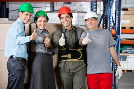 Portrait of happy foremen and supervisors gesturing thumbs up at warehouse - shallow depth of field, focus on thumbs Stock Photo