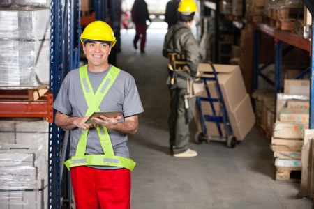 Portrait of happy mid adult foreman with digital tablet and coworker pushing handtruck at warehouse Stock Photo - 16056552