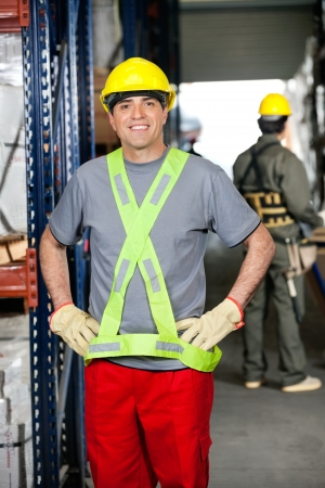 Portrait of happy mid adult foreman with hands on hips and coworker pushing handtruck at warehouse photo