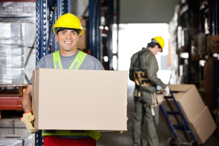 handtruck: Portrait of happy mid adult foreman with cardboard box and coworker pushing handtruck at warehouse