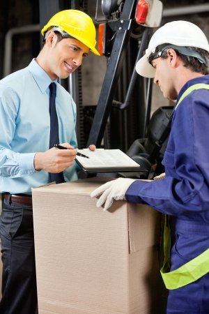 Young male supervisor showing clipboard to mid adult foreman at warehouse Stock Photo - 16056498