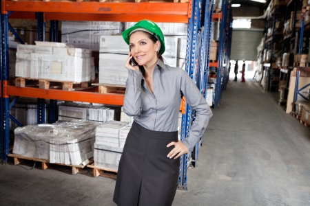 formals: Young female supervisor in formals using cell phone at warehouse