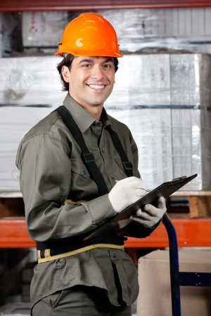 work safety: Portrait of happy male supervisor writing on clipboard at warehouse Stock Photo