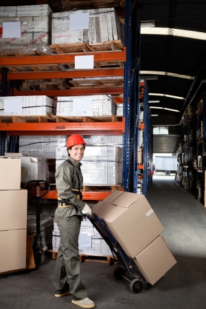 Portrait of young foreman pushing handtruck with cardboard boxes at warehouse photo