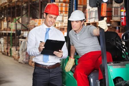 supervisores: Supervisor de joven que muestra portapapeles capataz en almacén Foto de archivo