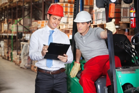 warehouse equipment: Young supervisor showing clipboard to foreman at warehouse Stock Photo