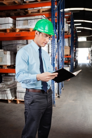 Young male supervisor reading book at warehouse photo