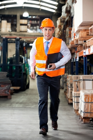 Portrait of young supervisor in a hurry at warehouse Stock Photo - 16056598