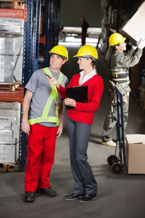 Young female supervisor instructing foreman at warehouse photo
