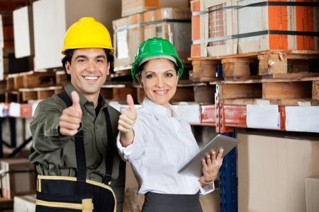 デジタル タブレットと職長ジェスチャー親指を倉庫で女性監督