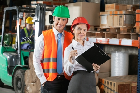 Portrait of two confident young supervisors with book clipboard at warehouse photo